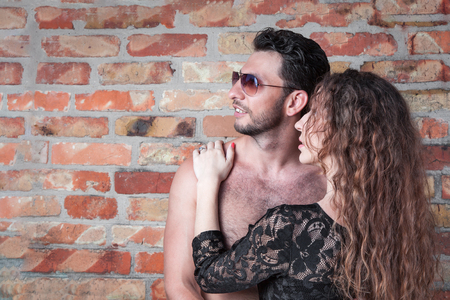 Young couple on a brick wall background looking into the distance Standard-Bild