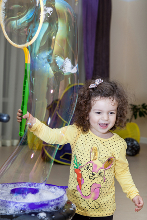 A little cheerful girl lets the soap bubbles in the room Standard-Bild