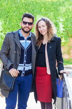 Portrait of loving couple outdoors, guy and girl in fashionable clothes are happy together