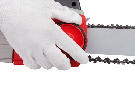 Workers arm pulls the chain on the electric saw, , isolated on white background with clipping path