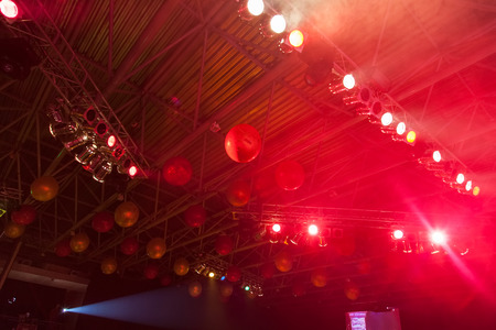 Ceiling decorated with balloons at the festival and beam of a searchlight