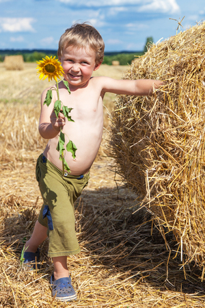 Young boy stands near a bale of straw with a blossoming sunflower in his hand