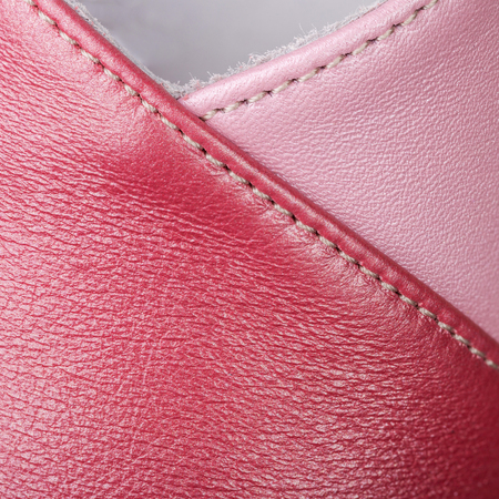 Fragments of stitched pieces of red and pink skin, natural texture closeup, abstract background, leather pattern