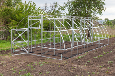 The frame of the greenhouse is installed in the garden in the spring, drip irrigation system mounted on the ground