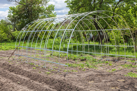 The frame of the greenhouse is installed in the garden in the spring Stock Photo