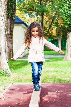 어린이는 놀이터에서 연습 균형, 공원에서 나무 빔에 소녀 놀이 균형