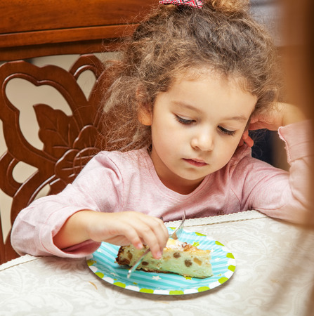 Portrait of a little girl with a cake at the dinner table