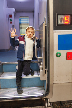 Boy waves his hand out of the train car, farewell gesture 版權商用圖片