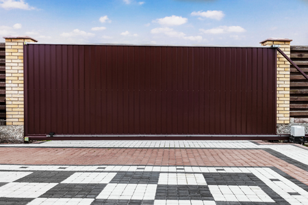 Modern garage door isolated on blue sky background with clipping paths.Large automatic sliding garage door, inside view. Archivio Fotografico