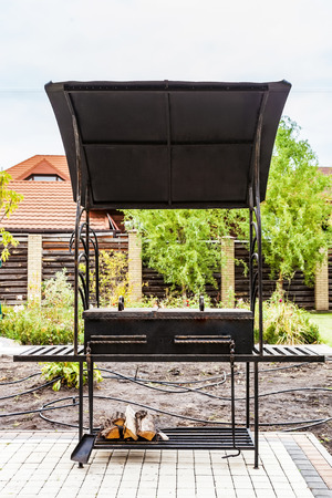 Metal barbecue grill with a canopy in the backyard Foto de archivo