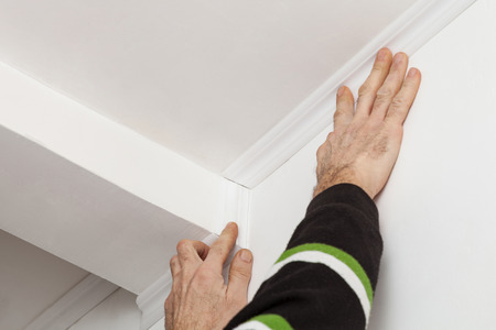 Installation ceiling moldings from white polystyrene foam