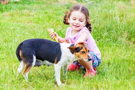 Happy little girl stroking mongrel dog outdoors Stock Photo
