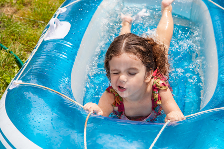 Baby girl playing in an inflatable boat full of water