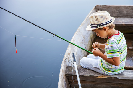 Young fisherman catches fish from boat on a fishing tackle, boy changes the bait on the hook