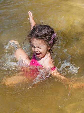 Little girl having fun bathing in the river