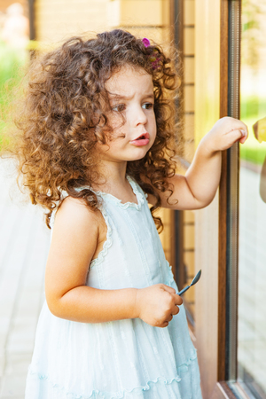 Little girl knocks on the closed door Banque d'images