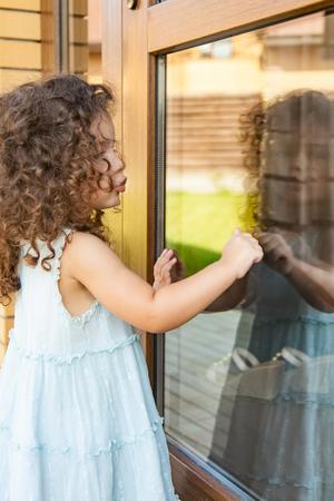 Little girl knocks on the closed door Banco de Imagens