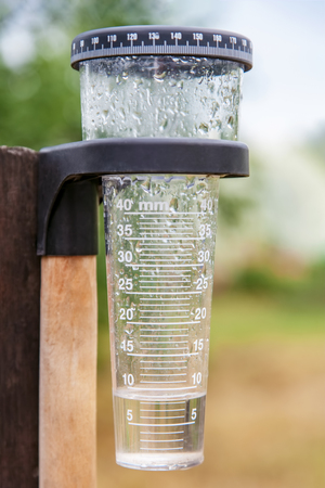 Meteorología con pluviómetro en jardín, medición de precipitación.