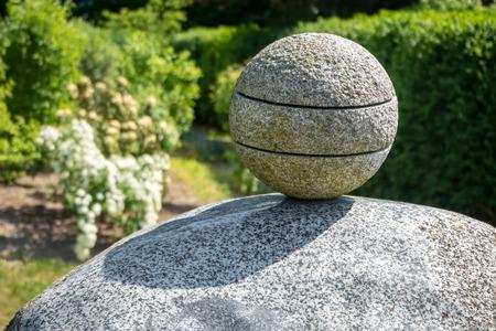 Stone ball on rock pedestal, garden sculpture
