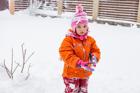 Baby girl muslim playing in the snow in winter outdoors