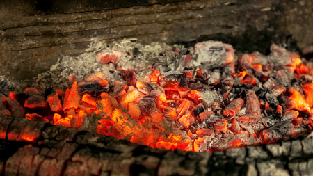 Burning firewood in the fireplace closeup, texture of fire and flame