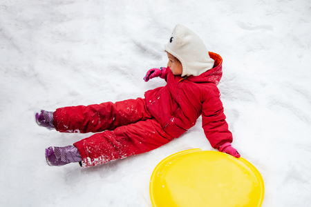 little girl with saucer sleds outdoors on winter day, ride down the hills, overturn on sleds,fell into the snow, winter games and fun Standard-Bild