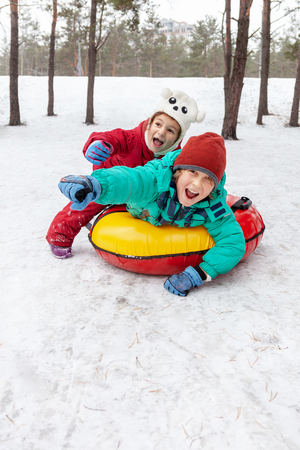 Boy and girl sliding down the hill on tubing sleds outdoors, winter day, ride down the hills, winter games and fun
