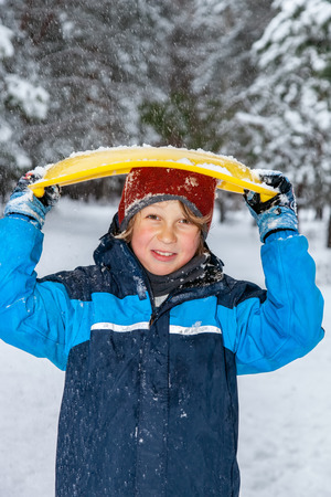 Closeup portrait of a boy in winter, covered his head with a snow saucer