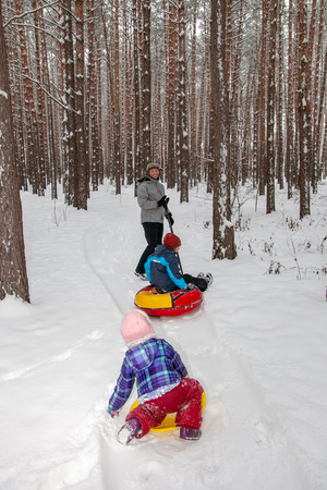 Father with children on a walk in the winter forest