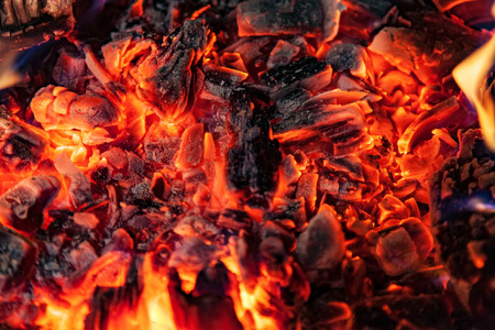 Glowing embers in hot red color, abstract background. The hot embers of burning wood log fire. Firewood burning on grill. Texture fire bonfire embers. Foto de archivo