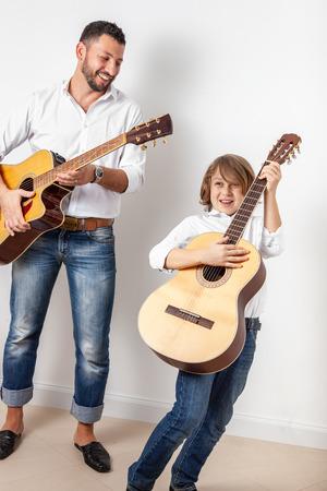Padre e hijo tocando guitarras en el interior, concierto en casa