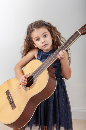 Baby girl playing acoustic guitar at home