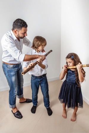 Father teaches son and daughter to blow bamboo flute 写真素材