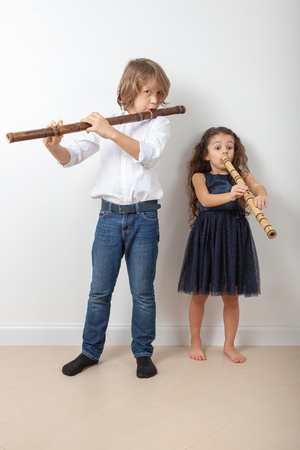 Boy and girl in white shirt plays bamboo flute indoors