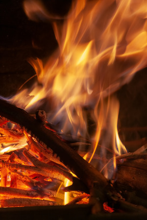 Burning firewood in the fireplace closeup, texture of fire and flame, dark background Stock Photo