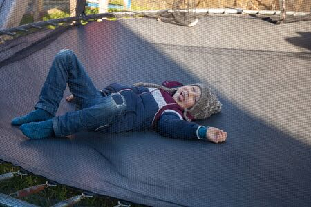 Satisfied boy is lying on the trampoline and smiling