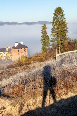 Foggy morning in the mountains, Ukraine, Carpathian Mountains, shadow of photographer in foreground