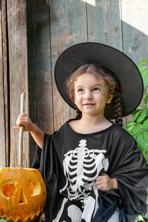 Halloween and celebration concept. Cute little girl in a witch costume holds a magic wand and conjures with halloween pumpkin outdoors