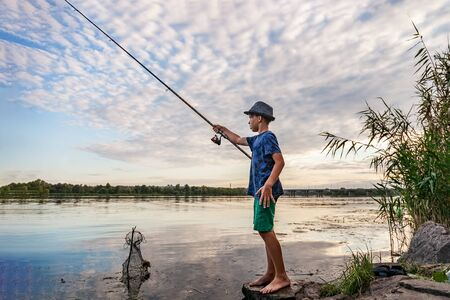 Boy with a fishing rod catches fish standing on the bank of the river