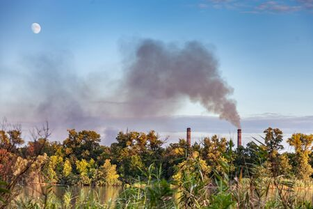 The smoking chimneys of a metallurgical plant against the backdrop of a beautiful landscape, environmental pollution
