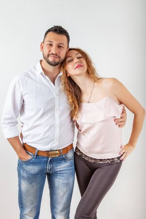 Young muslim man hugs a european girl on a white background, couple in love posing hugging in studio