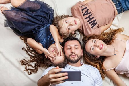 Happy family taking selfie picture with smartphone at home, mother, father, son and daughter, holidays, technology and people concept