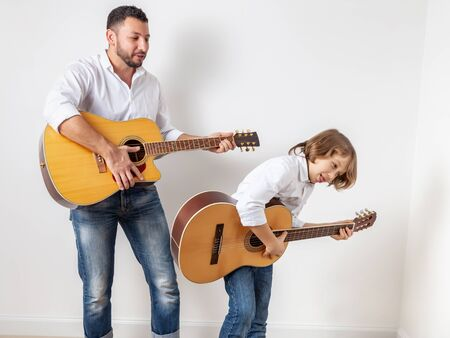 Father and son playing guitars indoors, home concert