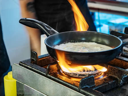 Chef cooking noodles and vegetables in a pan on fire, pasta with cream in frying pan on fire and flames. Street food Banco de Imagens