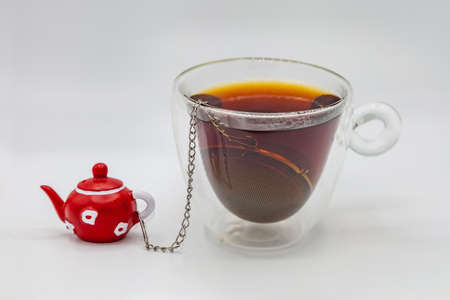 Cup of tea with tea strainer and a small decorative teapot on a chain isolated on white
