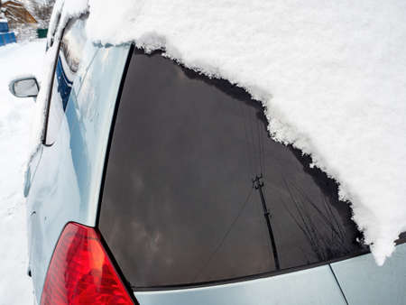 The back of the car covered with snow close-up, reflections in the glass and a brake light