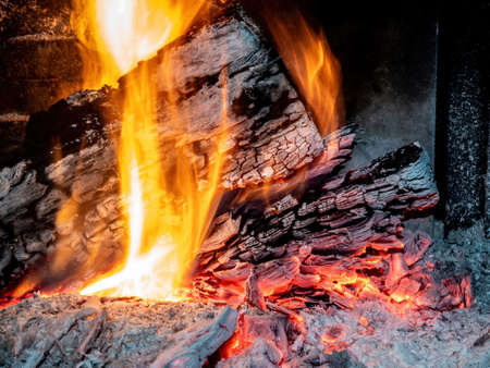 Burning firewood in the fireplace close up as abstract background
