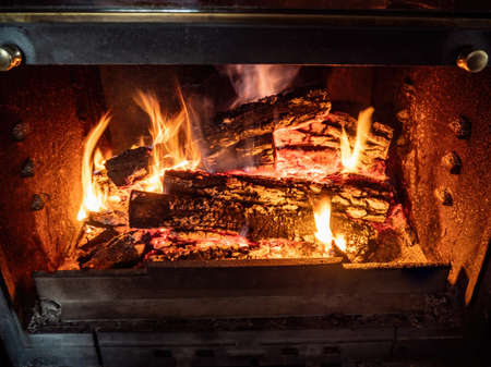 Burning firewood in the fireplace closeup