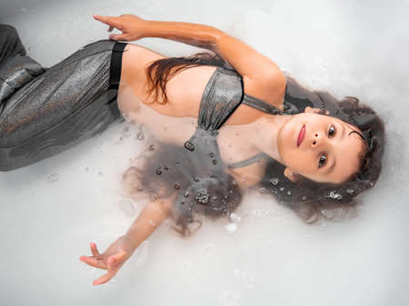 Baby girl with long hair in a mermaid costume lying in the water in the bathtub Foto de archivo