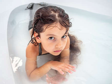 Baby girl with long hair in a mermaid costume lying in the water in the bathtub and looks into the camera